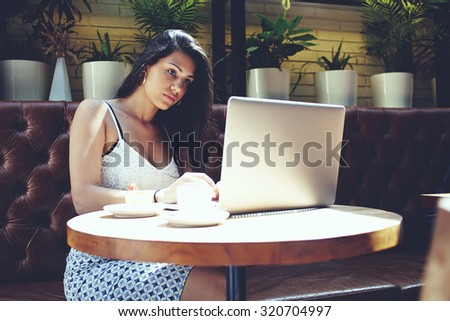 Successful businesswoman working on laptop computer and enjoying coffee with delicious cake, charming hispanic female sitting in beautiful modern cafe interior using net-book during morning breakfast - stock photo
