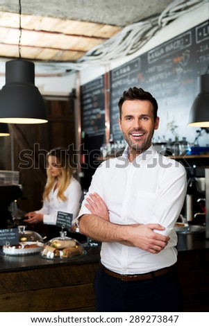 Successful cafe owner standing with crossed arms with employee in background preparing coffee - stock photo