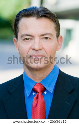 Successful caucasian business man, mature looking, posing in front of a office area outdoors - stock photo
