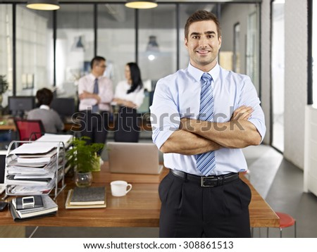 successful caucasian expat businessman standing in office arms crossed with with local colleagues talking in background. - stock photo