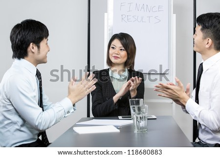 Successful Chinese business woman clapping and congratulating her colleagues. - stock photo