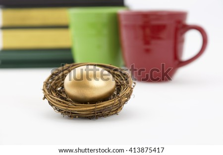 Successful, collaborative investment reflected in two coffee mugs, red and green, and books with selective focus on gold nest egg.  Education, due diligence. and winning strategy in symbols.  - stock photo