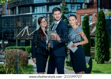 Successful company. Three confident businessman holding tablets and mobile phones in their hands in front of the office building and looking forward. Successful young people in a strict dress - stock photo