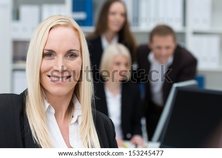 Successful confident beautiful businesswoman with a warm smile and long blond hair posing in an office with her colleagues in the background - stock photo