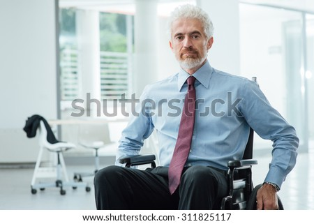 Successful confident businessman in wheelchair smiling at camera, career and disability overcoming concept - stock photo