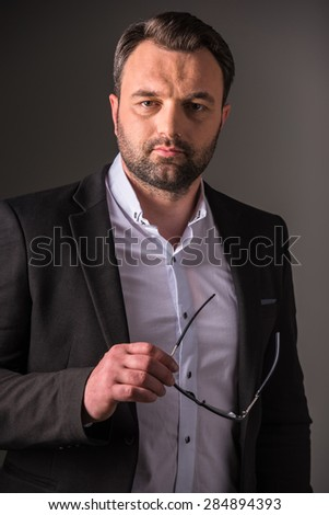 Successful confident businessman looking at camera on dark background. - stock photo