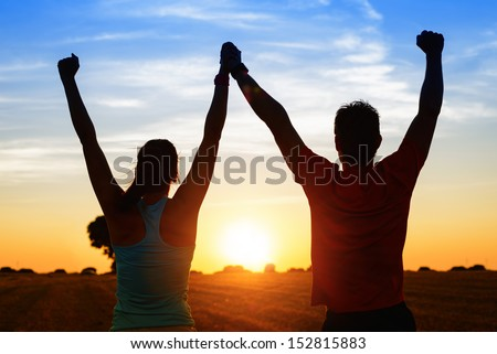 Successful couple of young athletes raising arms to golden summer sunset sky after training. Fitness man and woman with arms up celebrating sport goals after exercising in countryside field. - stock photo
