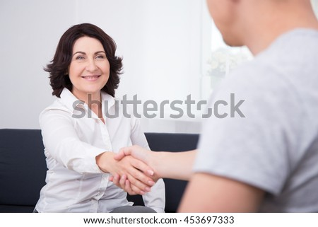 successful deal - businessman and businesswoman shaking hands in office - stock photo