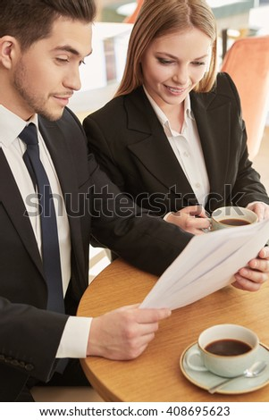 Successful deal. Vertical shot of a businessman and a businesswoman working with papers at the local coffee shop - stock photo