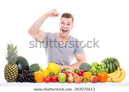 Successful Diet -  Handsome muscular man sitting behind a row of fruits and vegetables and raising his fist for success, isolated on white background - stock photo