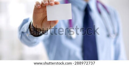 Successful doctor with business card - stock photo