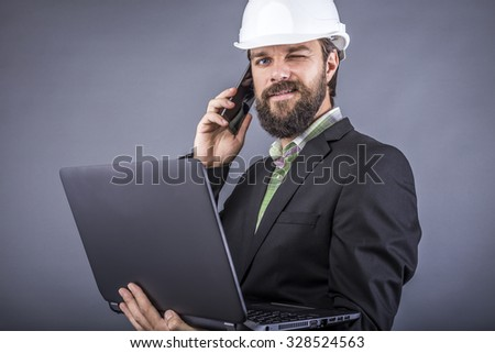 Successful engineer talking on the phone and holding his laptop over gray background - stock photo