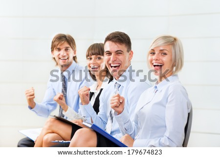 Successful excited Business people group team, young businesspeople smile hold fist ok yes gesture sitting in row line at office desk - stock photo