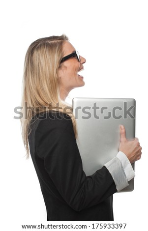 Successful female business executive standing holding her laptop computer to her chest and laughing with her mouth open in celebration, side view isolated on white - stock photo
