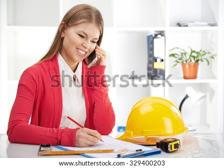 Successful female engineer drawing house draft and talking on phone with customer. Woman multi-tasking.  - stock photo