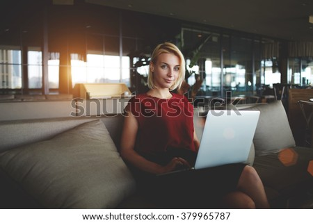 Successful female restaurateur with laptop computer waiting for business partners while sitting in office interior, young woman employer posing during work on net-book in modern comfortable cafe - stock photo
