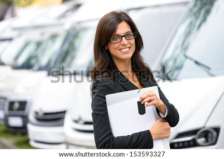 Successful female sales representative in van transport trade fair. Commercial exhibition and rental vehicle concept. Beautiful female seller or salesman holding car keys. - stock photo