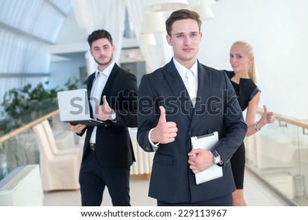 Successful finalizing the project. Young motivated businessman is standing with tablet and confidently shows than project is well done, two his business colleagues are standing on the background - stock photo