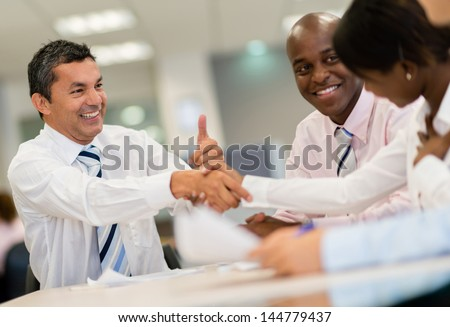 Successful group of business people closing deal with a handshake - stock photo