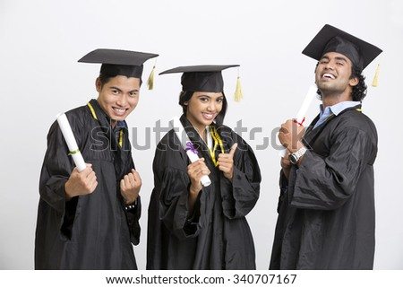 Successful group of Indian college graduates wearing cap and gown holding diploma on white background - stock photo