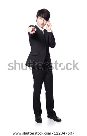 Successful handsome business man speaking mobile phone and finger pointing to you in full length isolated on white background, mode is a asian male - stock photo