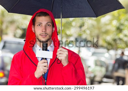 Successful handsome male journalist in red rain jacket working in rainy weather outdoors in park environment holding microphone and umbrella in live broadcasting. - stock photo