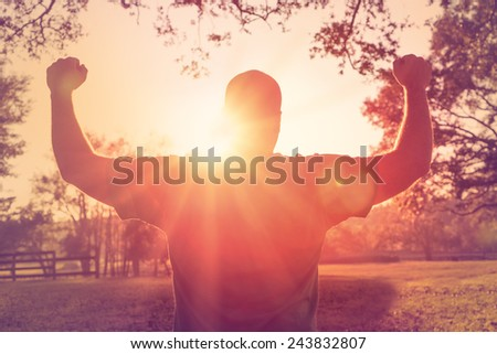 Successful happy accomplished man stands with raised arms facing the sun. White male athlete with arms up celebrating and happy with his achievement and exercise. - stock photo