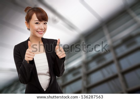 Successful happy Asian businesswoman showing thumb isolated on business background. - stock photo