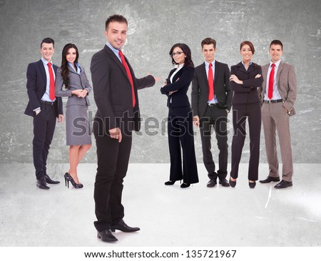 Successful happy business team being presented by a young leader, on gray background. young business man welcoming you to his business team - stock photo