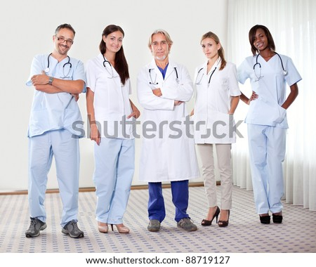 Successful happy group of doctors with stethoscope at the hospital - stock photo