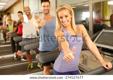 Successful happy people smiling thumbs up in gym. - stock photo