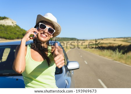 Successful happy woman on cellphone call enjoying summer car travel vacation and doing approval positive gesture with thumbs up. Female traveler  on roadtrip in Spain. - stock photo