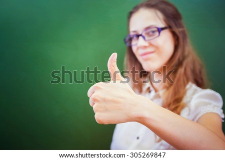 Successful happy young teacher or student at university or school classroom near a blackboard and show a thumbs up gesture. Selective focus on the hand - stock photo