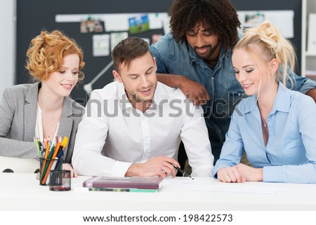 Successful hardworking young diverse business team working on a project together grouped around paperwork on the desk - stock photo