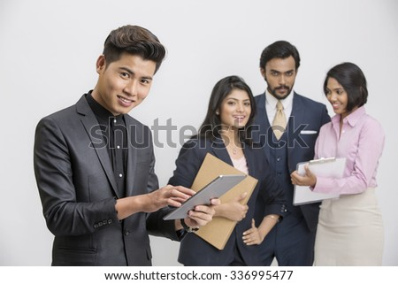 Successful Indian businessman working in tablet with his busy colleagues on white background. - stock photo