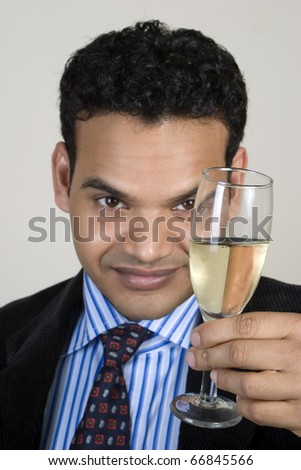 successful Indian celebrating with a drink - stock photo