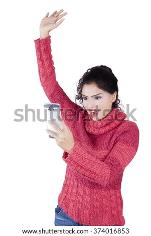 Successful Indian woman reads message on the cellphone while raising hand and wearing winter clothes in studio - stock photo