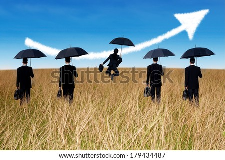 Successful insurance agent with umbrella and arrow up on the field - stock photo