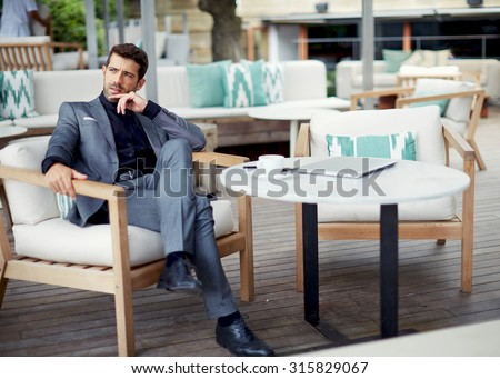 Successful intelligent business man relaxing in a luxury restaurant outdoors, confident thoughtful entrepreneur, wealthy men pensive rest and waiting someone in the modern coffee shop terrace - stock photo