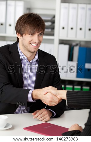 Successful job interview - happy businessman shaking hand and smiling. - stock photo