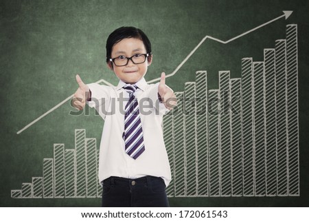 Successful little businessman showing thumbs up over a business chart - stock photo