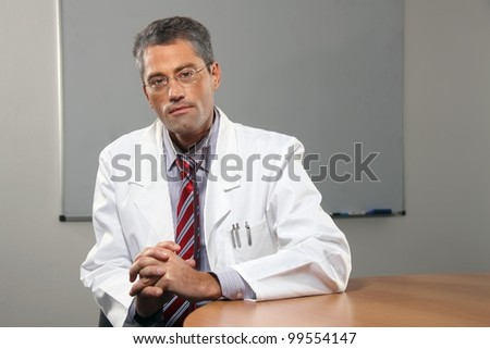 successful male doctor in his office - stock photo