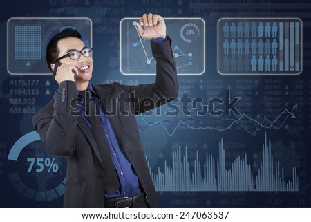 Successful male entrepreneur talking on the phone near the financial statistics - stock photo