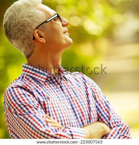 Successful man concept. Portrait of smiling happy mature man in trendy casual shirt & stylish glasses looking up and posing in the park. Sunny summer day. Copy-space. Close up. Outdoor shot - stock photo