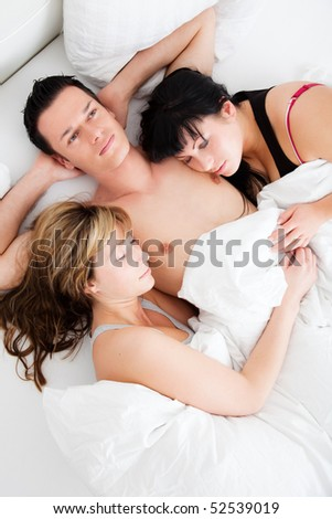 Successful man lying with two girls in bed - stock photo