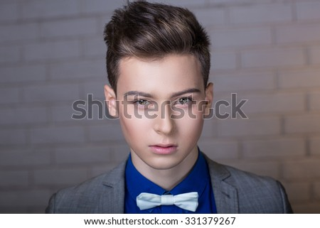 Successful man. Portrait of perfect style person. Stylish short hair dress, white brick wall background. Think new idea how to create new fashion project or go to party, prepare to New Year evening - stock photo