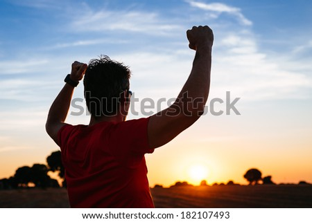 Successful man raising arms after cross country running on summer at sunset. Male athlete with arms up celebrating success and freedom after sport exercising and working out. - stock photo