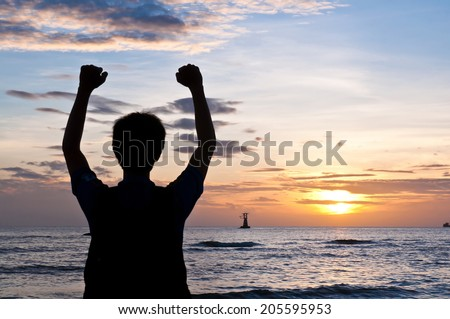 Successful man raising arms on the beach sunset - stock photo