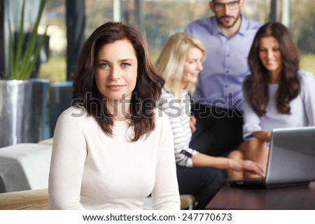 Successful mature business woman sitting at meeting while colleagues working on background. Teamwork. - stock photo
