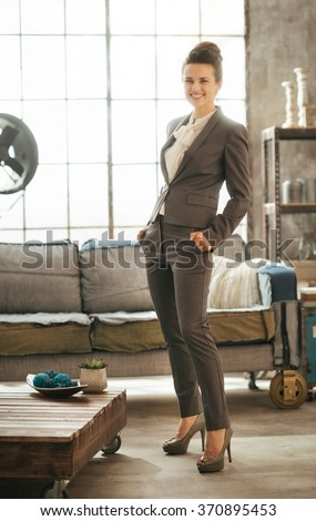 Successful modern business woman freshen up before work in her perfect loft apartment. Portrait of stylish smiling businesswoman in business suit - stock photo